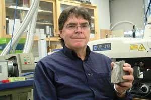 James Fassett avec un os fossile de dinosaure à la main.